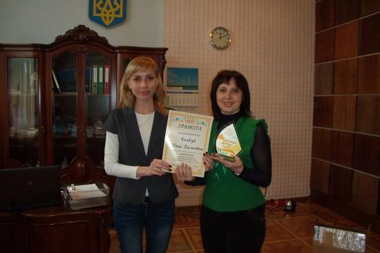 Керівник БКЦ Олена Карнелос ліворуч, наророджує переможця конкурсу